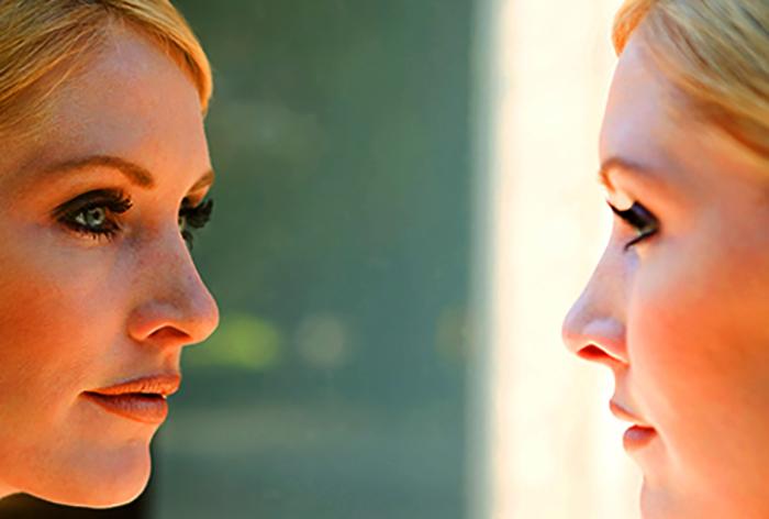 Девушка со здоровым лицо смотрит в зеркало