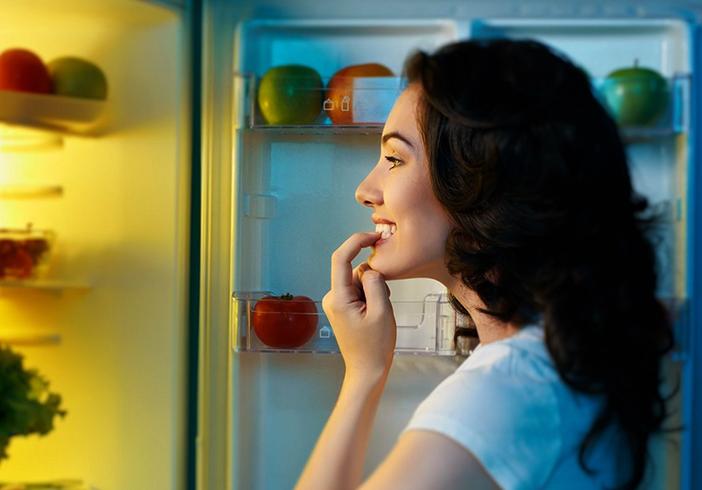 Женщина перед холодильником