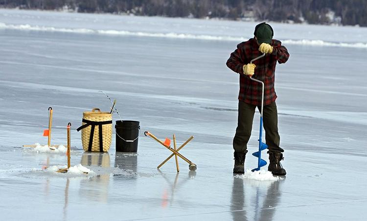 Рыбак делает прорубь
