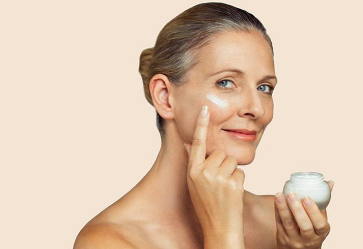 Женщина использует крем для лица