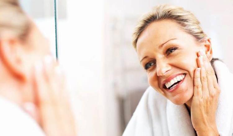 40-летняя женщина смотрит в зеркало